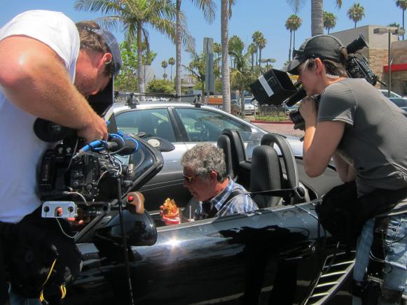Tony Bourdain eating in the car