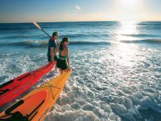 couples walking in the ocean