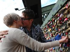Couple kisses with their love padlocks