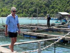 Tony Bourdain walking past the fish shop in Penang