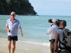 Anthony Bourdain walks on the beach on Monkey Island