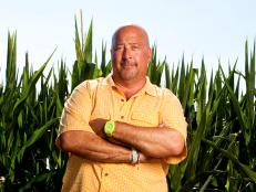 Andrew Zimmern stands in a field of corn in Iowa
