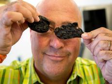Andrew Zimmern holds octopus bile sacs.