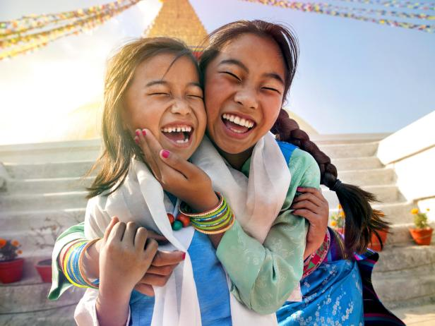 two sisters smiling, boudha temple, nepal, sun soaked,