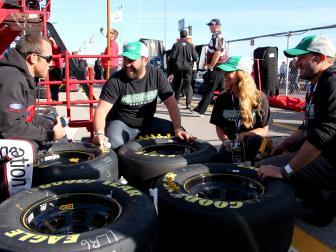 nascar, three men, woman, working on tires