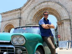 man leaning on vintage car in cuba