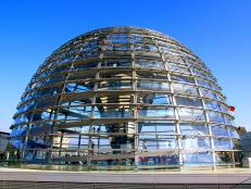 tall clear dome with spiraling staircase on top of government building in berlin during daytime