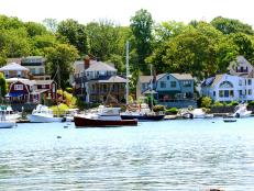boats in harbor during the day with houses along the shore