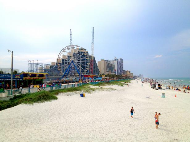 view of beach with people, ocean, and amusement park rides, ferris wheel