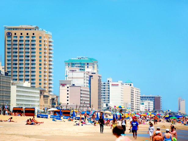 busy scene on a beach with tourists and buildings on the left during the daytime