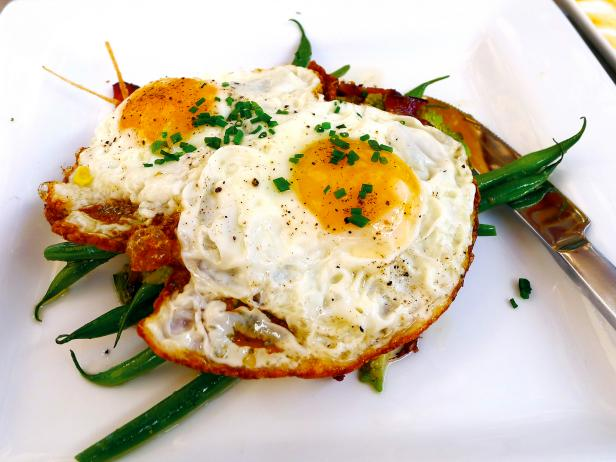 close up off fried eggs with chives and green beans white plate
