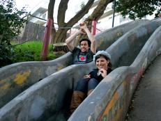 Couple sliding down slides at Seward Mini Park in San Francisco