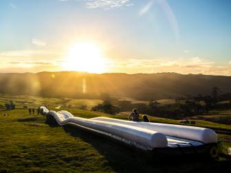extremely long waterslide, sunset, greenery, very large field, mountains