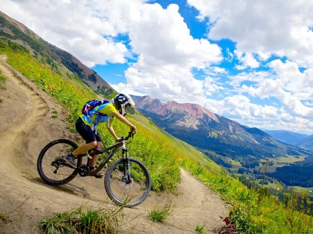 young boy rides mountain bike down trail with mountains in background on sunny day