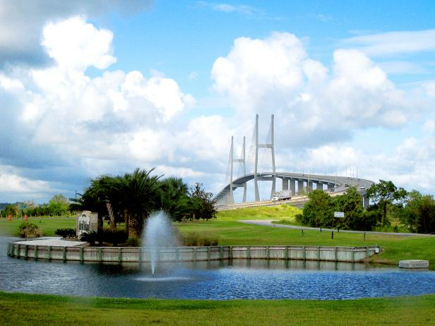 park with fountain in front of a tall bridge in background in daytime