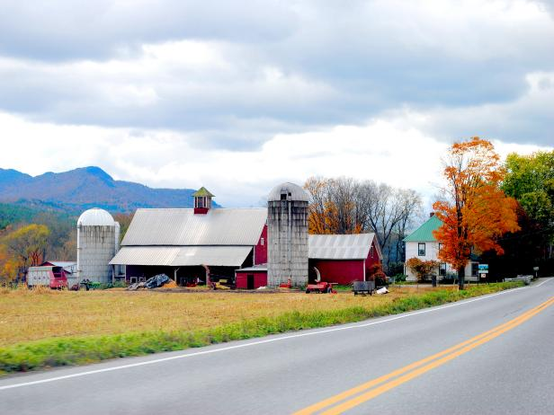 farm on left side of road during the fall with leaves changing colors and overcast sky