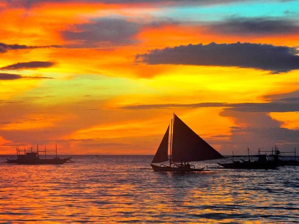 sunset with ships on ocean in the philippines