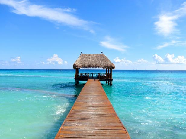 dock leading to covered cabana in the sea in the caribbean cancun